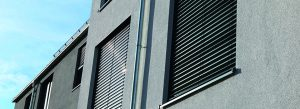 geschlossene Rolladen an grauer Hausfassade